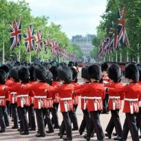 British guardsmen march down the Mall in London  - outside Buckingham Palace. British national (Union Jack) flags fly to celebrate the Queen's birthday